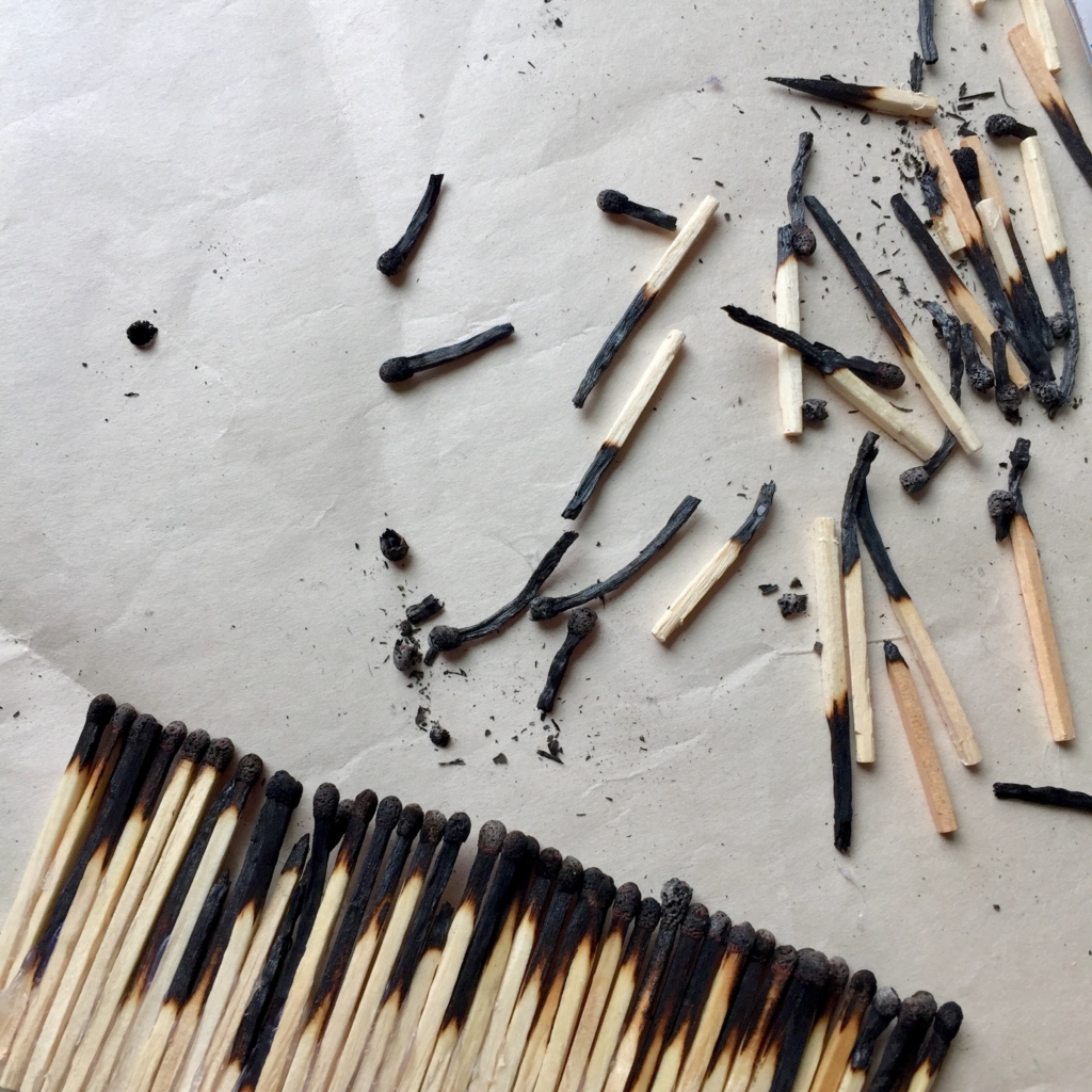 Broken used matches on a grey piece of paper